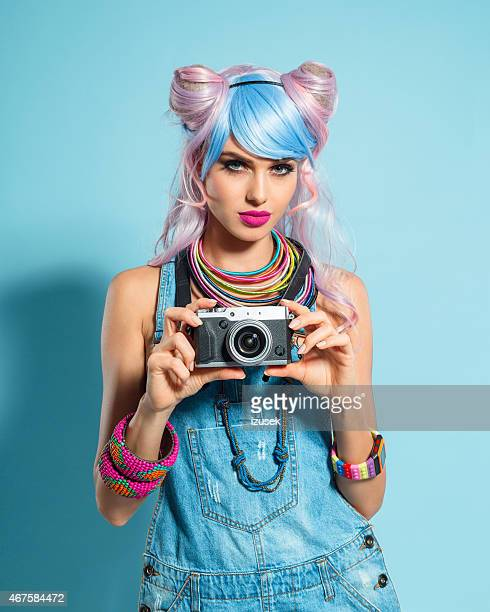Pink hair girl in funky manga outfit holding camera