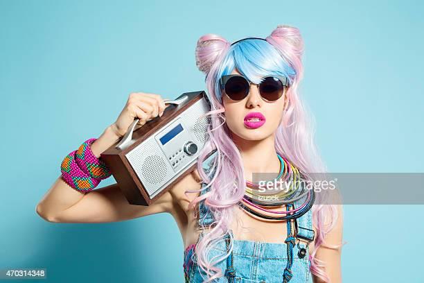 ラジオを保持しているファンキーなマンガの衣装でピンク髪少女