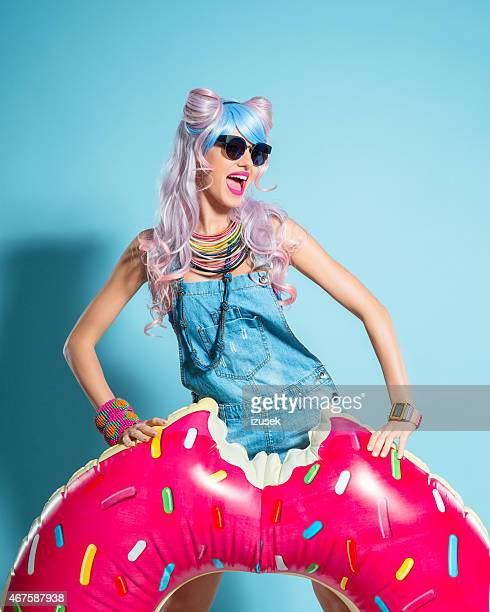 Pink hair girl in manga outfit posing with inflatable donut