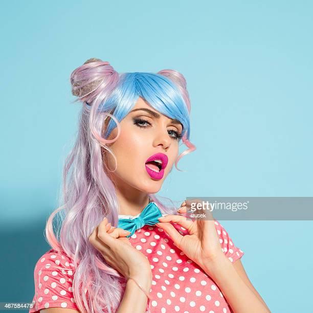 Cheveux teints en rose Bande dessinée japonaise fille tenant un noeud papillon