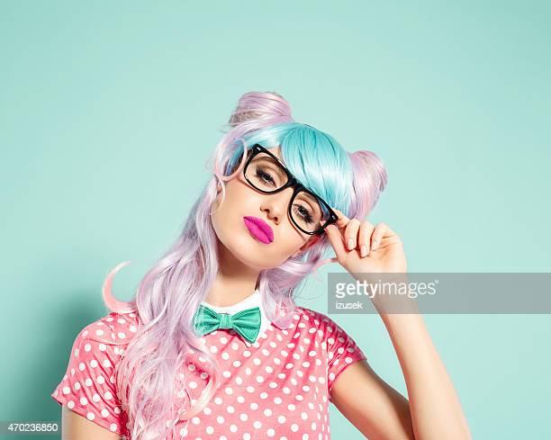 Fille de style manga cheveux roses tenant des lunettes nerd