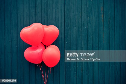 Pink Heart Shape Balloons Against Blue Wooden Wall