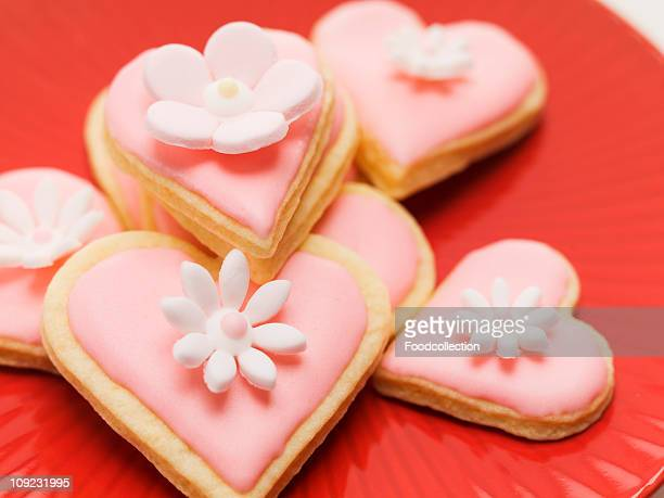 Pink heart shaped biscuits with sugar flowers, close-up