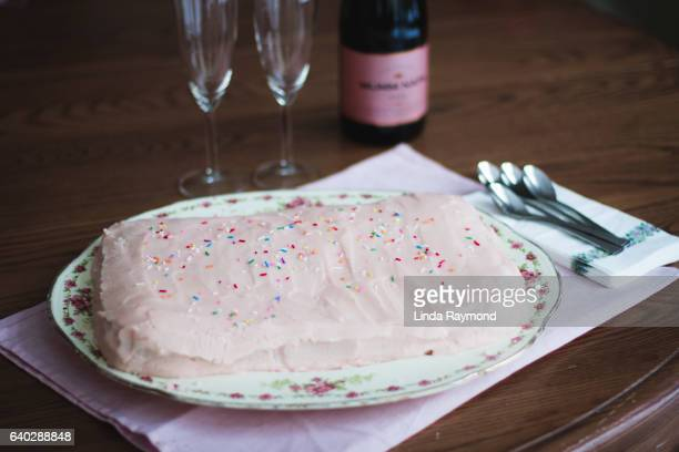 Pink home made cake with champagne and glasses beside