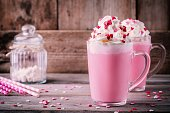 Pink hot milk with whipped cream and sugar hearts in a glass mug for St. Valentine's Day