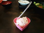 Pink ice cream served in small  heart shaped container for dessert treat with spoon and blur background of other dishes on table.
