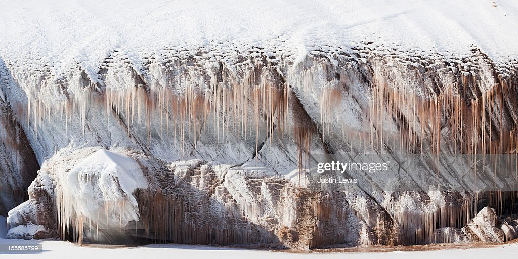 Pink icicles hang from snowy ice cave : Stock Photo