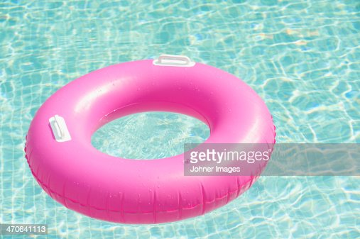 Pink inflatable ring floating at swimming pool