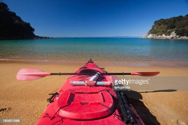 Pink kayak on sandy beach shore