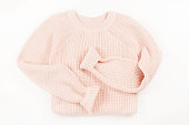 Pink knit sweater flat lay on white background. Top view