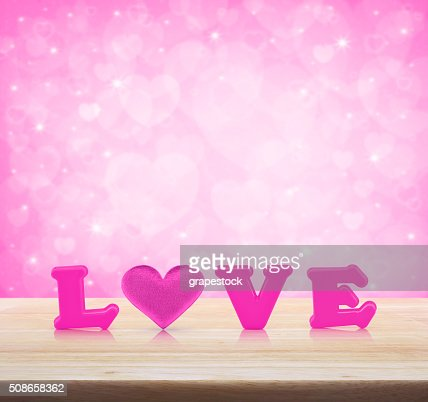 Pink love alphabet and fabric heart on wooden table : Stock Photo