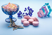 Macaroon cakes with colorful fluffy marshmallows in blue vase over blue background.