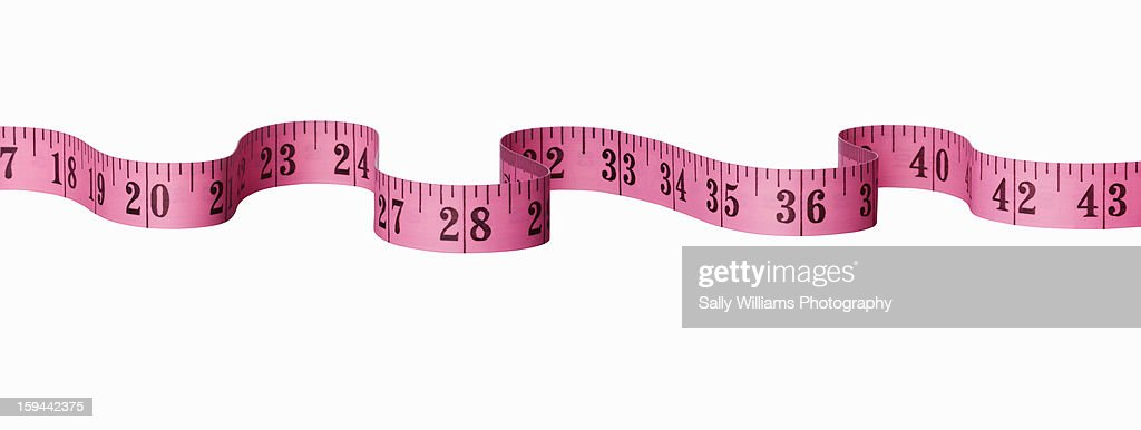 A pink measuring tape on a white background : Stock Photo