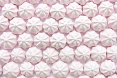 Pink strawberry mini meringues as food background. Top view.