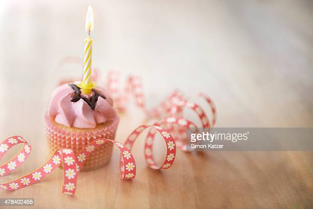 Pink muffin with burning candle