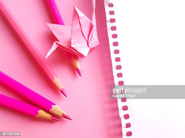 Pink origami and colored pencils