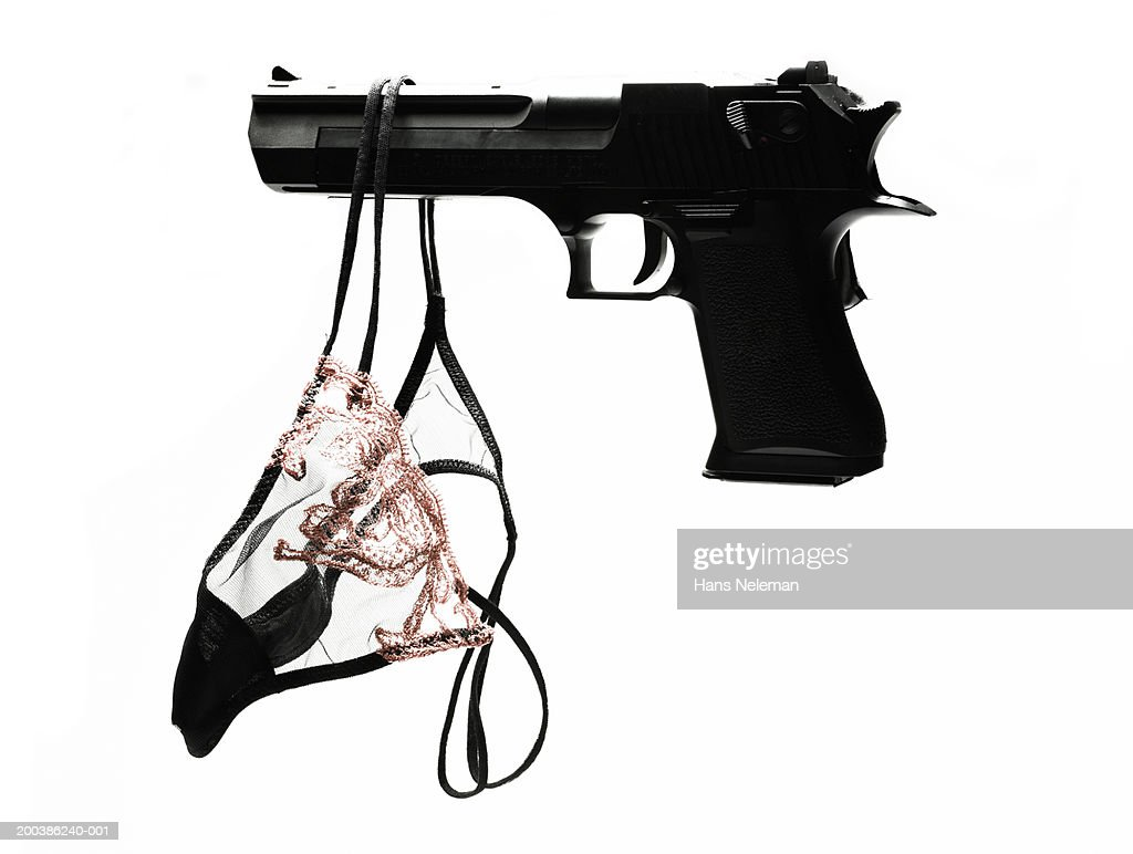Pink panty hanging from black gun, overhead view