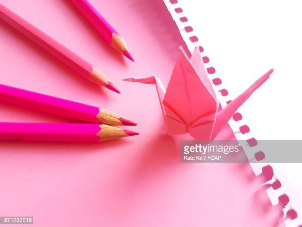 Pink paper crane and colored pencil