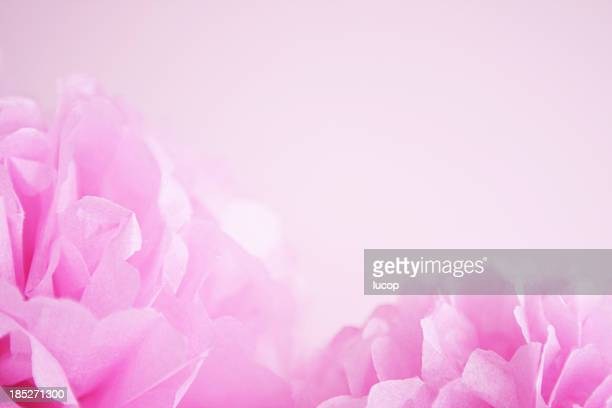 Pink paper pom pons on pink background