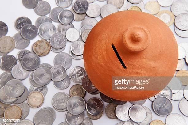 Pink piggy bank standing on coins heap