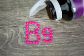 Pink pills forming shape to B9 alphabet on wood background