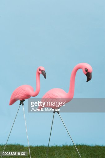 Pink plastic flamingoes on grass