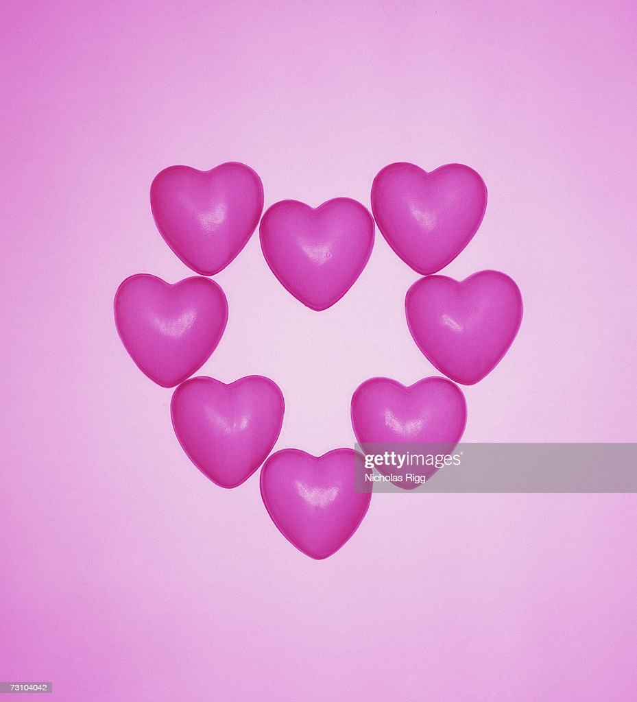 Pink plastic hearts on coloured background, close-up : Stock Photo