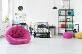 Pink pouf and toys in scandi kid's room with knot pillow on bed with patterned bedsheets
