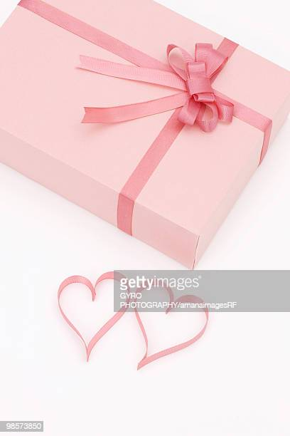 Pink present and ribbons in shape of hearts