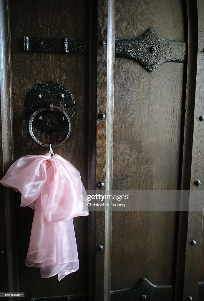 A pink ribbon, representing the favourite colour of missing 5 year old April Jones, hangs on the door of St Peters Church on November 1, 2012 in Machynlleth, Wales. Coral and Paul Jones, the parents of missing April, have thanked the public for their 'kind words and sentiments' which have provided support in the month that has passed since her abduction.