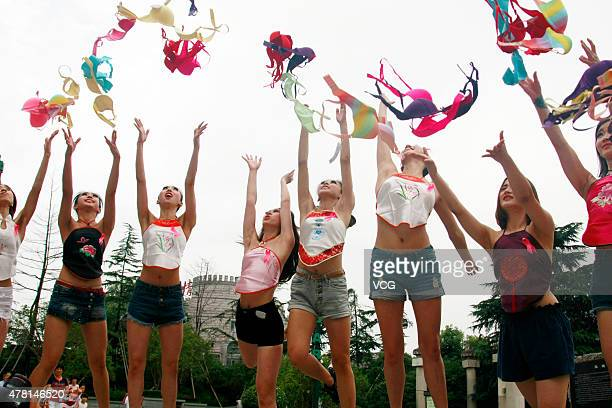 Pink Ribbon volunteers throw up bras to raise women's attention on breast health on a public service activity at Song Dynasty Town on June 22 2015 in...