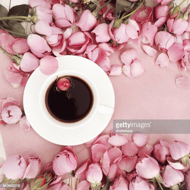 Pink rose flower and coffee on pastel background. Flat lay