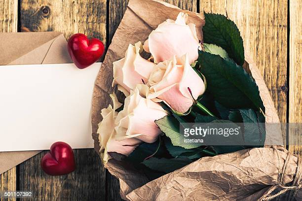 Pink roses and two red hearts on a rustic wooden board. Envelope and empty blank card for message on Valentine's Day