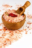 Pink salt from the Himalayas on white background. Pile of pink Himalayan salt. Salt and chilli peppers. Sale of spices.