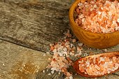 Pink salt from the Himalayas on wooden background. Pile of pink Himalayan salt. Sale of spices.