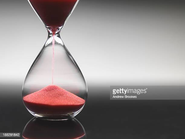 Pink sand pouring through hourglass