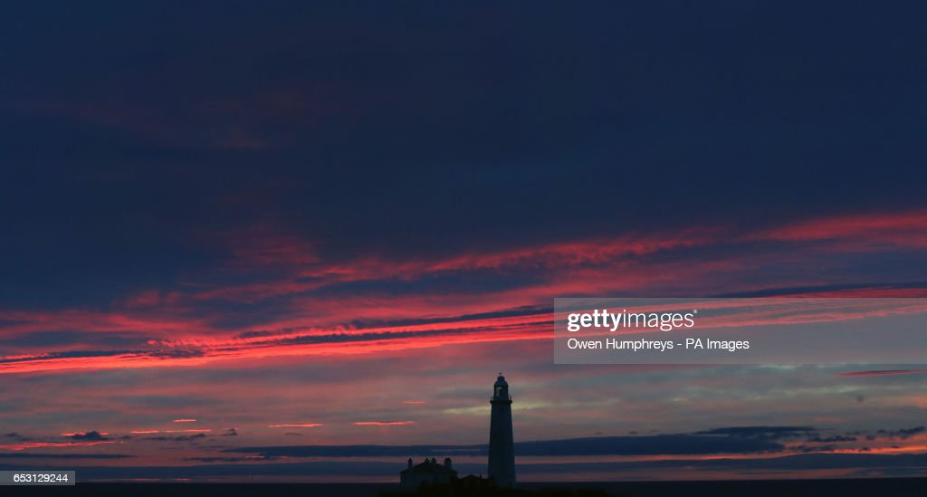 A pink sky before sunrise at St Mary's Lighthouse just off the North East coast, as parts of the UK will be as warm as Spanish hotspots Ibiza, Barcelona and Madrid today.