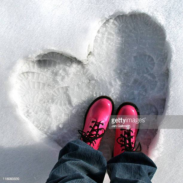 Pink snowboots in snow heart