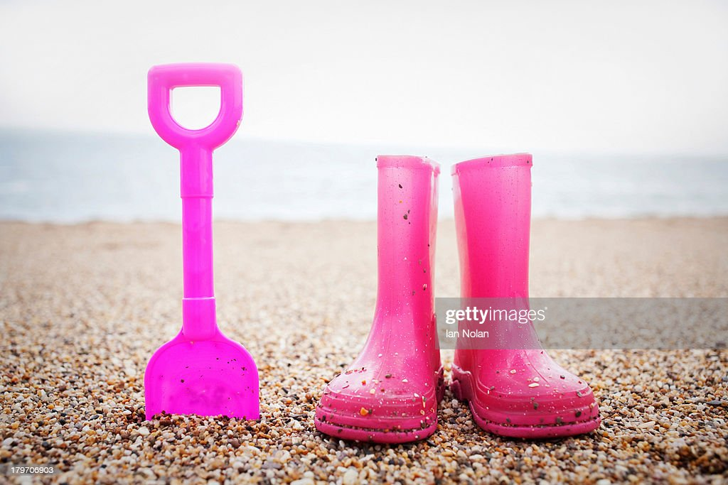 Pink spade and wellington books standing on beach