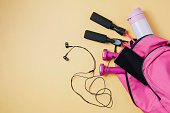 Pink sports bag and accessories on yellow background