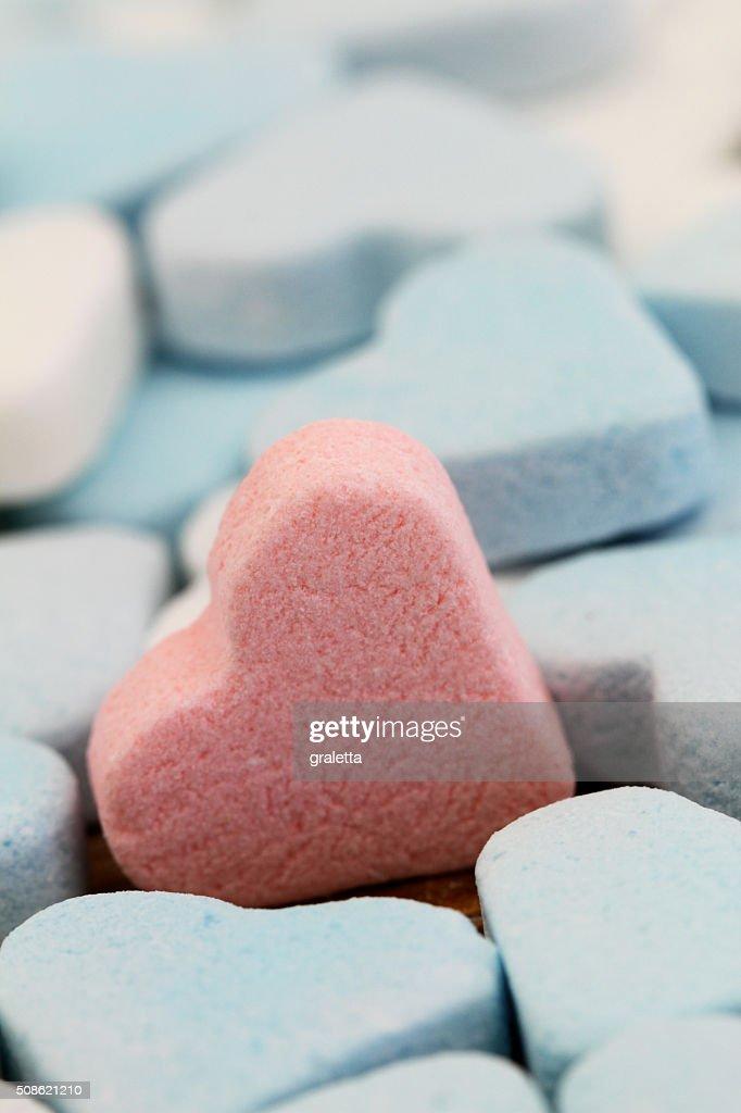 Pink sugar heart among white and blue sugar hearts : Stock Photo