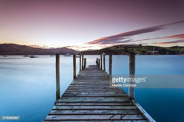 Pink sunset over jetty and blue lake, New Zealand
