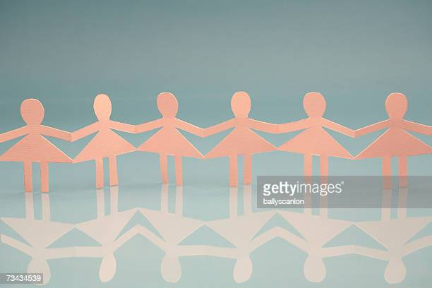 Pink woman paper chain dolls on blue background