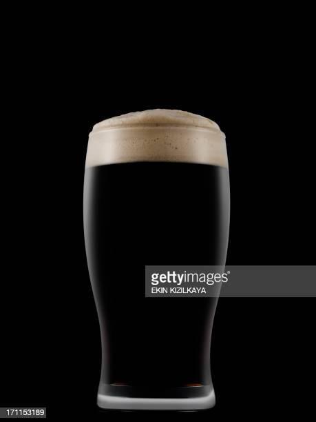 Pint glass full of dark beer on a dark background