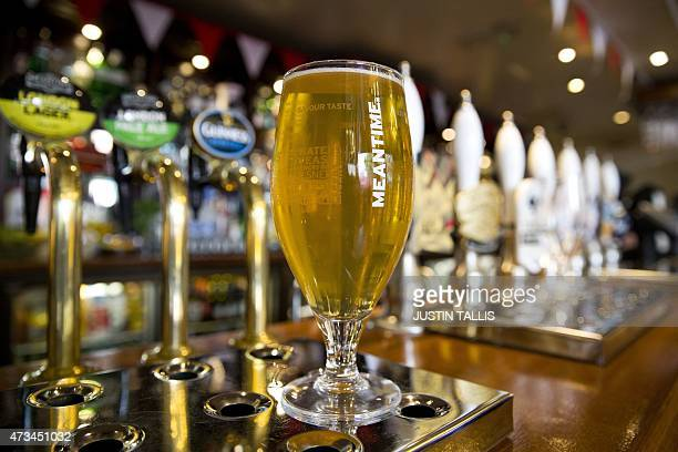 A pint glass of beer with the logo of Meantime a London based craft brewing company stands at the bar of a pub in London on May 15 2015 SAB Miller...