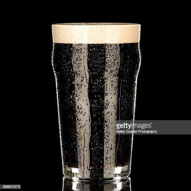 Pint glass of chilled stout with black background