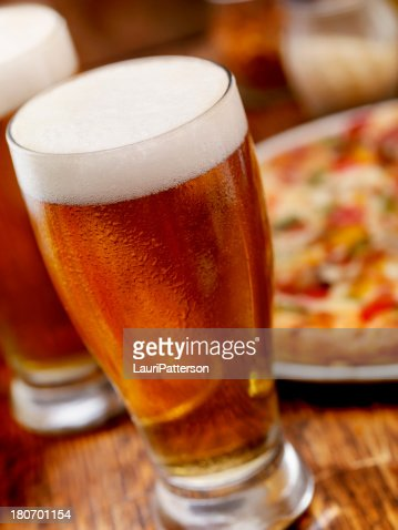 Pint of Beer and a Deluxe Pizza : Stock Photo