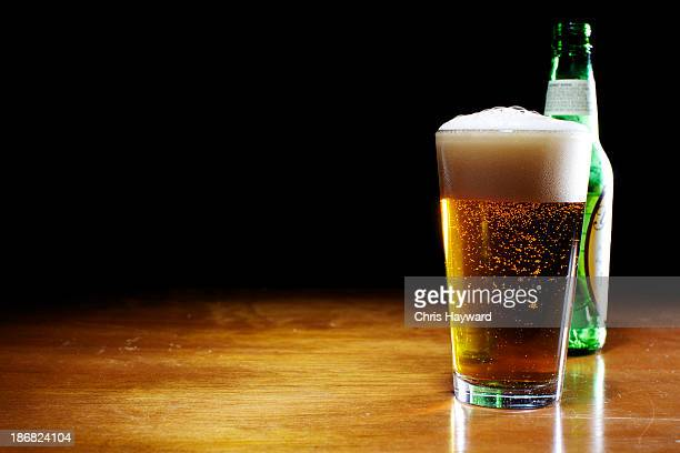 A pint of beer next to a bottle on a wooden table