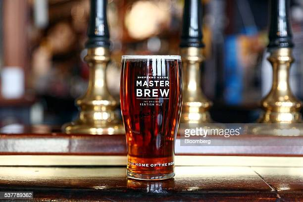 A pint of Master Brew ale brewed at the Shepherd Neame Plc brewery stands on the counter at The Bear Inn pub in Faversham UK on Friday April 22 2016...