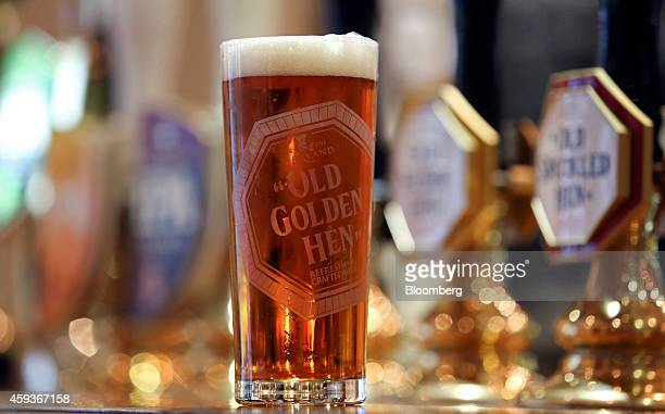A pint of 'Old Golden Hen' ale produced by Greene King Plc stands on the bar at the company's brewery in Bury St Edmunds UK on Wednesday Nov 19 2014...